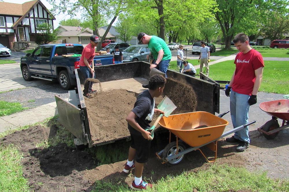 People shoveling dirt into a wheel barrow